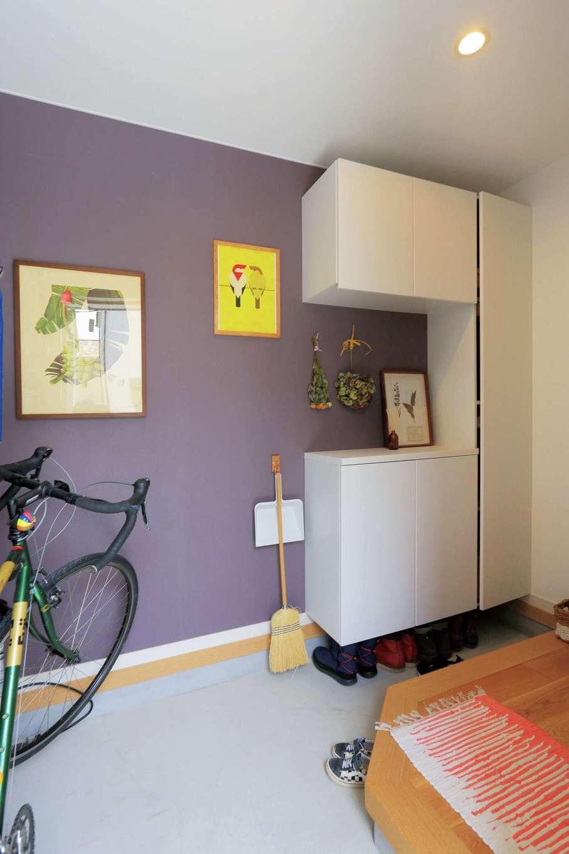 小幡建設【デザイン住宅、収納力、省エネ】自転車を置くため広めの土間に。カラーバランスの良いパープルの壁がシック。シンプルなディスプレイが似合う
