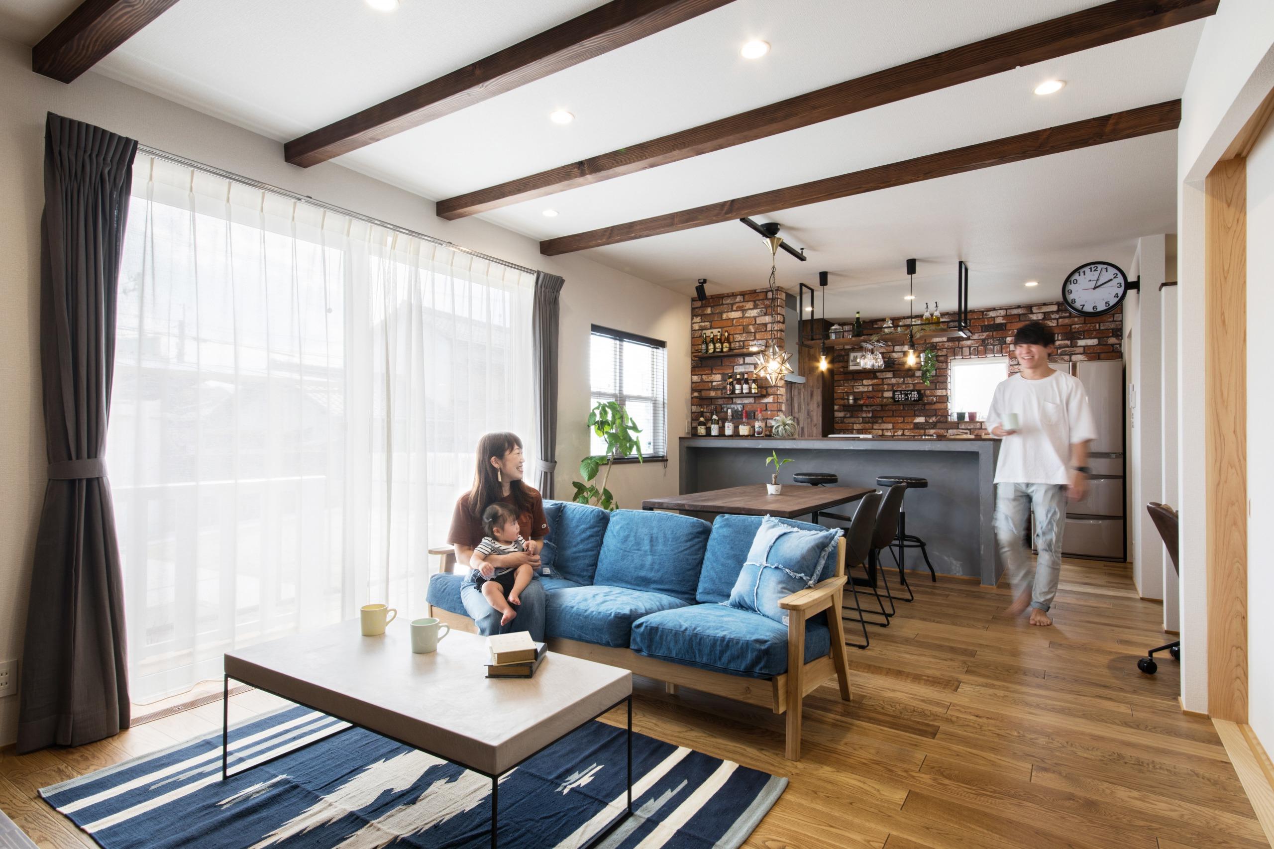 小幡建設【デザイン住宅、収納力、省エネ】モルタル調キッチンは、本物のレンガを貼った壁やアイアンラックが見事に調和。夫妻ともに大好きだと言う、お酒の瓶が並ぶ様子も絵になる。またキッチン奥には古材調に仕上げた造作収納や、大容量のパントリーがあり、物が増えがちなキッチンまわりもスッキリ