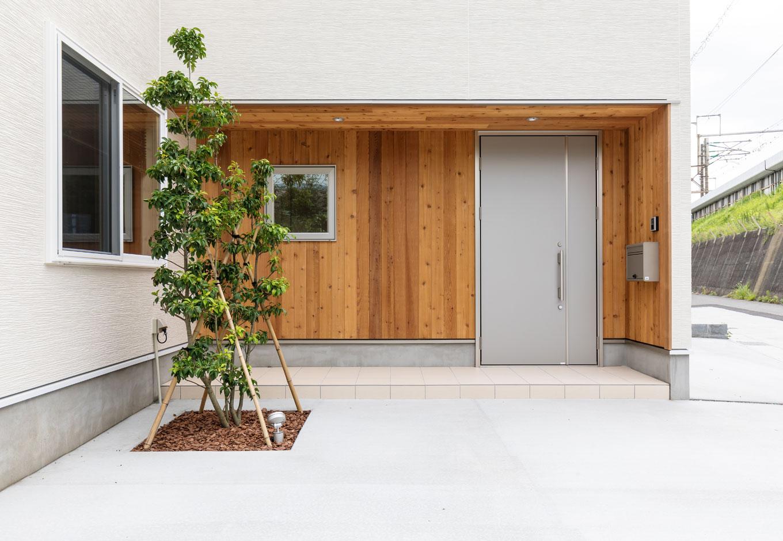 無垢材を張った玄関まわりが印象的。シンボルツリーは、家の中からの見え方にもこだわって植栽の場所を細かく指示した