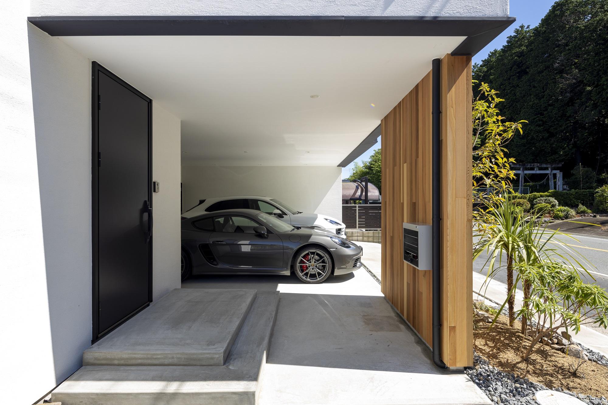 スタイルカーサ【デザイン住宅、趣味、屋上バルコニー】vacancesシリーズskygarageの特徴はこのビルトインガレージ。車から玄関、玄関から郵便受けまで雨に濡れずに行けるのが嬉しい。玄関ポーチのモルタル仕上げもスタイリッシュなデザインになっている