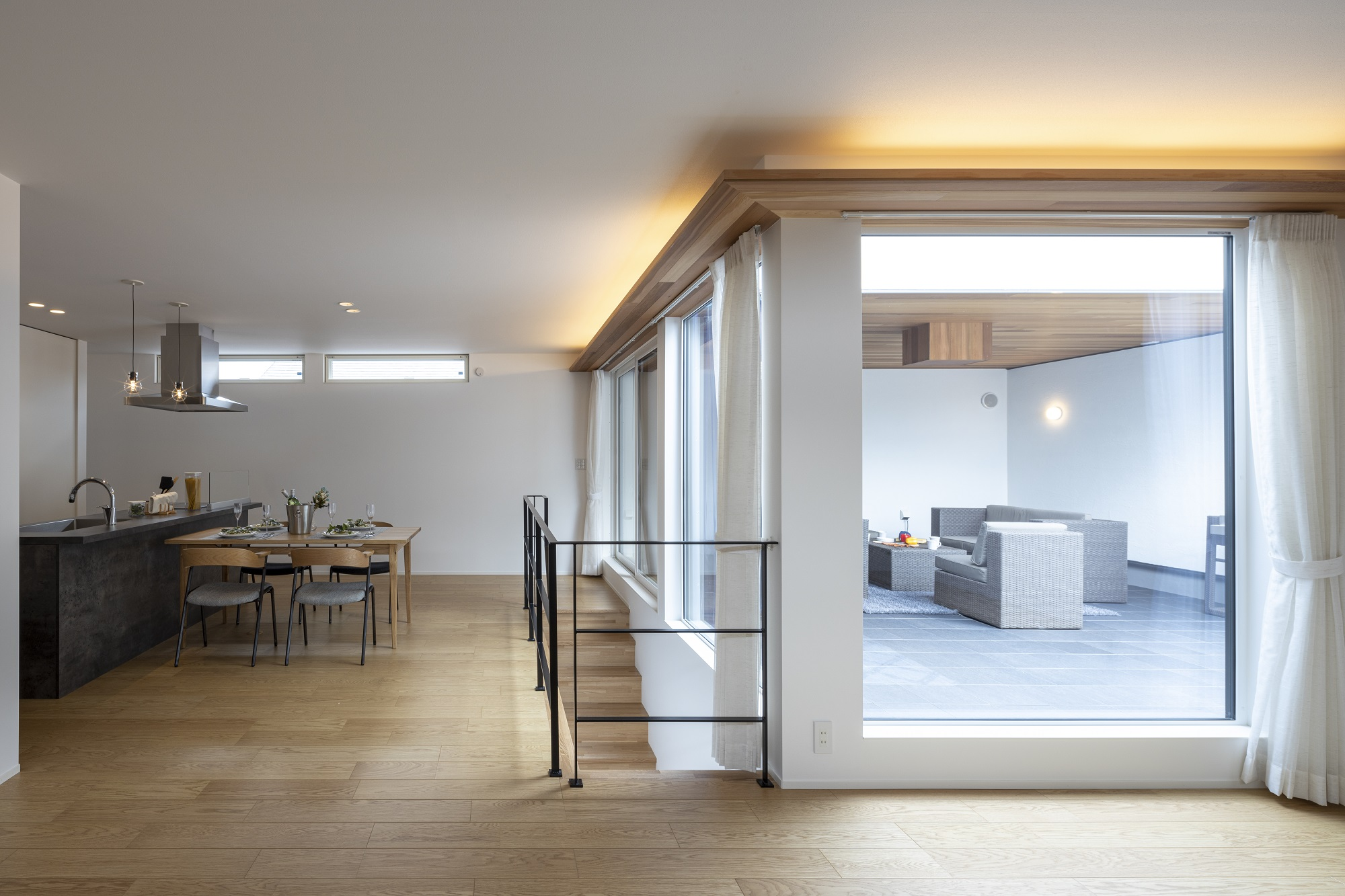 スタイルカーサ【デザイン住宅、趣味、屋上バルコニー】LDKとスカイテラスのつながり。2Fのどこにいてもお互いを感じられる空間になっている。スカイテラスから続くレッドシダー張りの天井は室内に入ったところで間接照明に。中で楽しみ、外で楽しむ