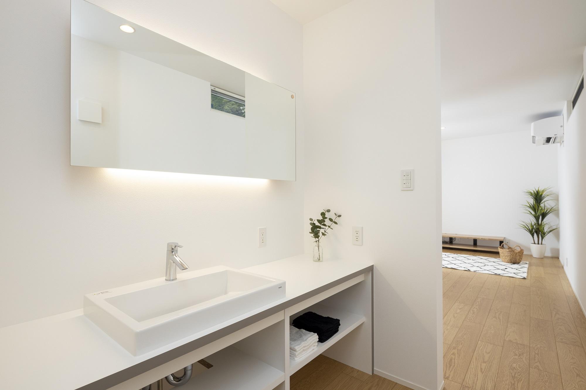 スタイルカーサ【デザイン住宅、趣味、屋上バルコニー】2Fの洗面はT様にイメージ写真を持ってきていただきそれを再現したそう。標準仕様のシンプルな洗面台に大きな一枚鏡に間接照明を組み込んだ