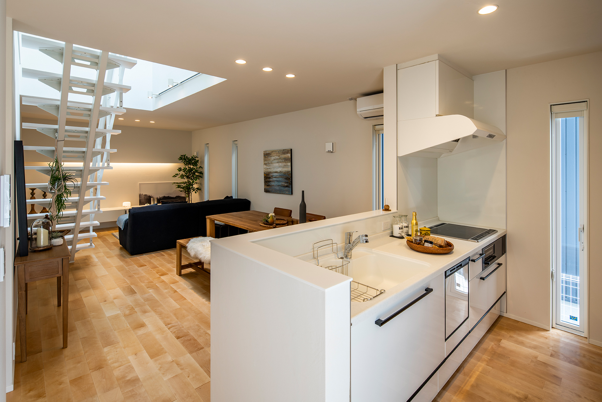 スタイルカーサ【デザイン住宅、間取り、インテリア】家族の様子を眺めながら料理できる位置にキッチンを配置。吹抜けを通して2階の気配がわかるので、子育てママも安心。肌触りのいい床は無垢のバーチ材で、時とともに飴色に変化していく