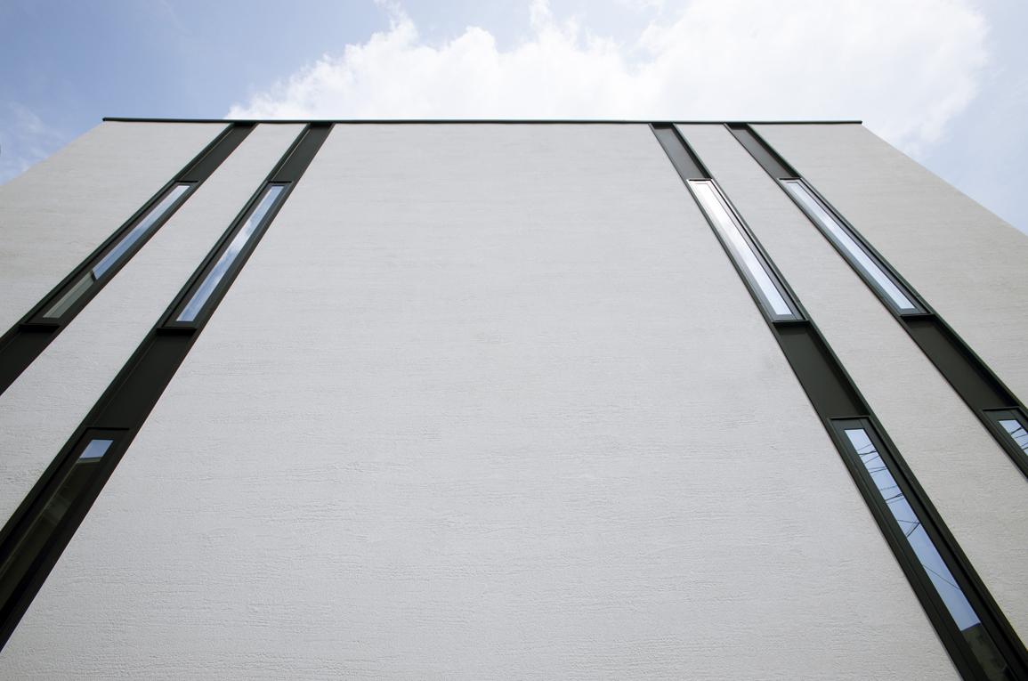 スタイルカーサ【デザイン住宅、間取り、インテリア】外壁は表情豊かな塗り壁仕上げ。2階の天井から1階の下まで細長いスリット窓が伸びているため、雨だれの汚れが目立ちにくく、長期間メンテナンス不要。幅12.2cmのスリット窓は、視線を遮りながら光と風を招き、プライバシーを確保できる。細く人が通り抜けられないので防犯性も高い