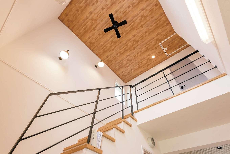 静鉄ホームズ【デザイン住宅、子育て、趣味】リビングの上部は窓から明るい光が差し込む吹き抜けにプラン変更。アイアンの手すりや天井に貼った木調のクロス、シーリングファンがリゾートのコテージのような雰囲気に