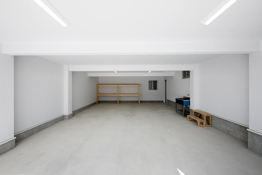 トーモク【子育て、収納力、自然素材】ガレージは車2台がラクラク駐車できる広さ。上階には収納スペースが設けられている