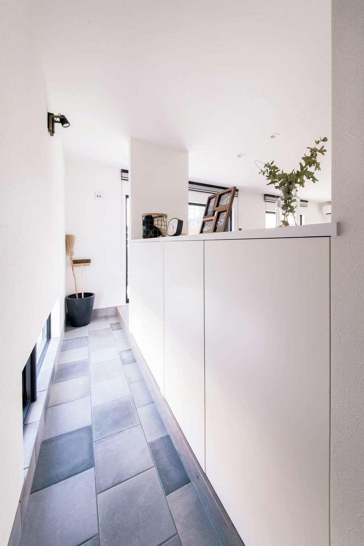 R+house 浜松中央(西遠建設)【デザイン住宅、子育て、建築家】玄関とリビングをつなぐ細長い土間が建物の奥行き感を強調。自転車置き場など多目的に使えるので便利。壁代わりの収納には家族分の靴がたっぷり収まる