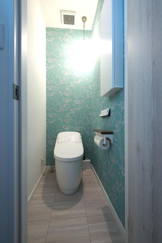 明和住宅【子育て、収納力、二世帯住宅】トイレ爽やかなアクセントクロスを用いた。ダウンライトはあえて壁側に寄せて、間接照明のようにしている