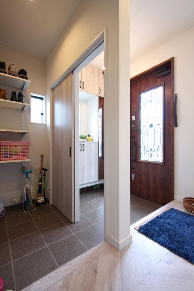明和住宅【子育て、収納力、二世帯住宅】土間収納玄関には土間収納を設けた。重厚感のある木製の玄関ドアは、奥さまのお気に入り。アイアン細工もかわいい