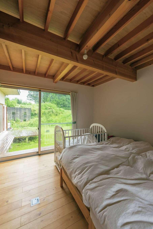 1階にある主寝室。夜はわずかな光が映し出す天井の木目を眺めながら眠り、朝、外を眺めれば緑が美しく、1日の終わりと始まりを心地よく過ごせる