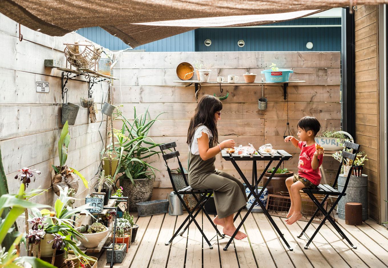 BESS浜松【趣味、自然素材、インテリア】キッチン横にまで伸びるウッドデッキにテーブルを持ち出して、朝食やおやつを楽しむ。テーブルを囲むようにある塀はHさんがDIYしたもの