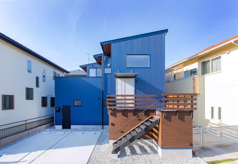 ARRCH アーチ【デザイン住宅、自然素材、建築家】ネイビーのガルバリウム鋼板が青空に映える。アプローチの階段や連続する勾配屋根のフォルムがスタイリッシュ
