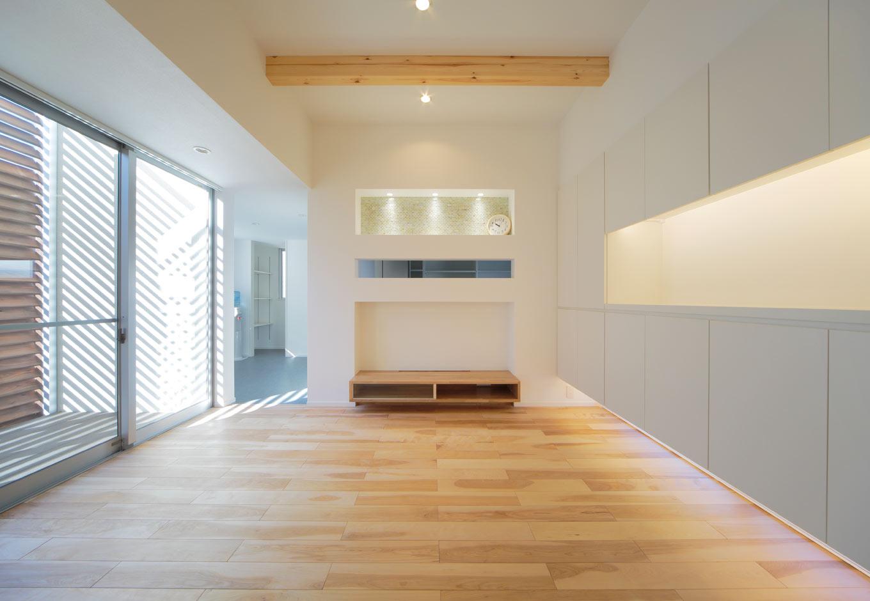 ARRCH アーチ【デザイン住宅、間取り、建築家】ルーバー越しにやわらかな光が差し込み、カバザクラの床材が足に気持ちいいリビング。右側の壁面収納の下に地窓を設けることで、室内に風が通る