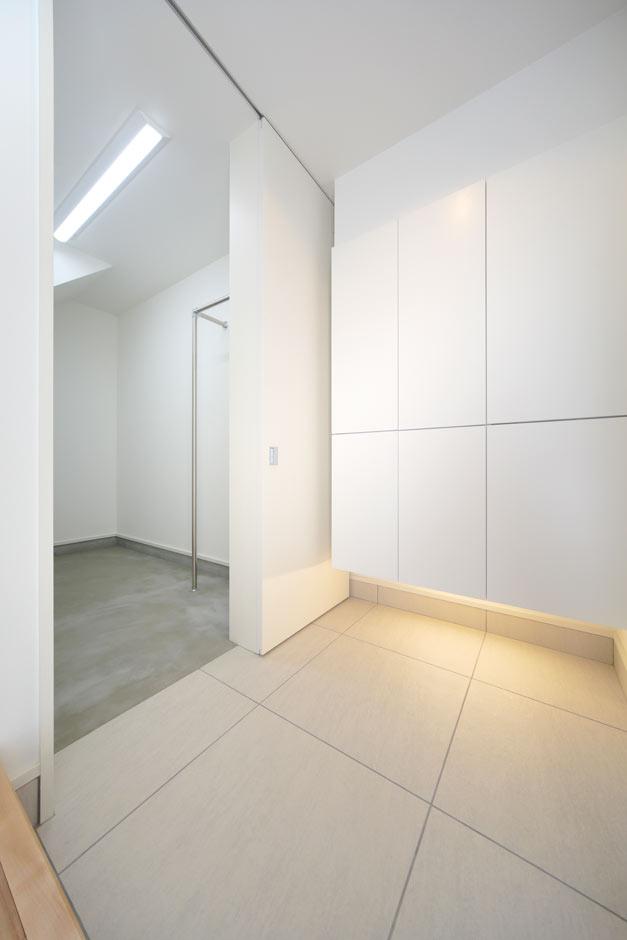 ARRCH アーチ【デザイン住宅、間取り、建築家】60cm x 60cmの大きなタイルを使った、ゆったりと上品な佇まいの玄関ホール。シューズボックスを浮かせ、照明を入れることで軽やかな印象に