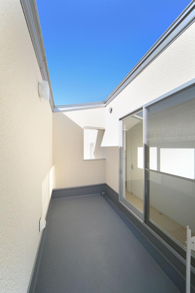 ARRCH アーチ【デザイン住宅、間取り、建築家】外壁を高く立ち上げ、外からの視線をカット。青空しか見えないバルコニーから、風や光が室内に届く