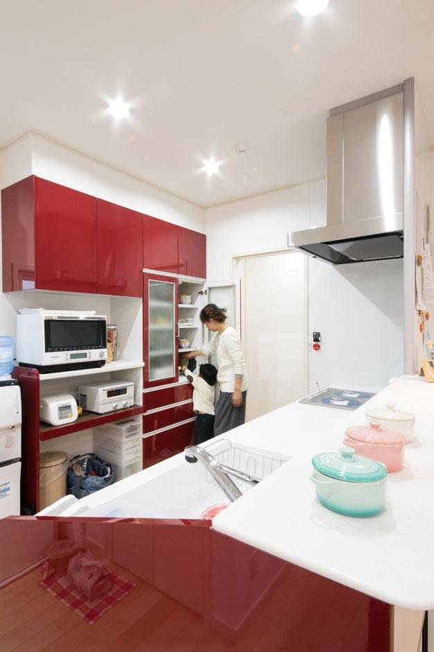 白をベースにしたLDKに、奥さまお気に入りの赤色のシステムキッチンが映える。扉の向こうは、回遊できる水回りスペース