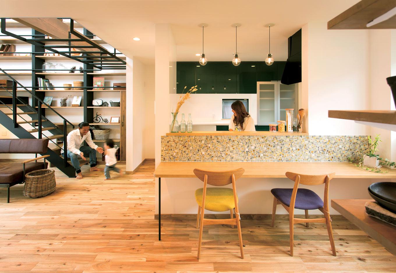 ARRCH アーチ【デザイン住宅、自然素材、間取り】普段リビングで食事をするHさんファミリーに、あえてカウンターキッチンを提案。気分が変わるだけでなく、調理中や片付けをする奥さまとの会話が自然とはずむ。グリーンをキーカラーにしたシステムキッチン、カフェっぽくカウンターにあしらったタイルなど、奥さまの好きがあふれる
