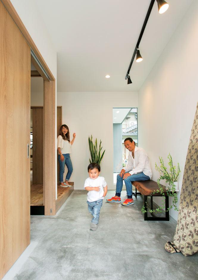 ARRCH アーチ【デザイン住宅、自然素材、間取り】玄関を開けると、窓の奥の坪庭まで土間玄関が続く。雨の日はお子さんの遊び場に変身