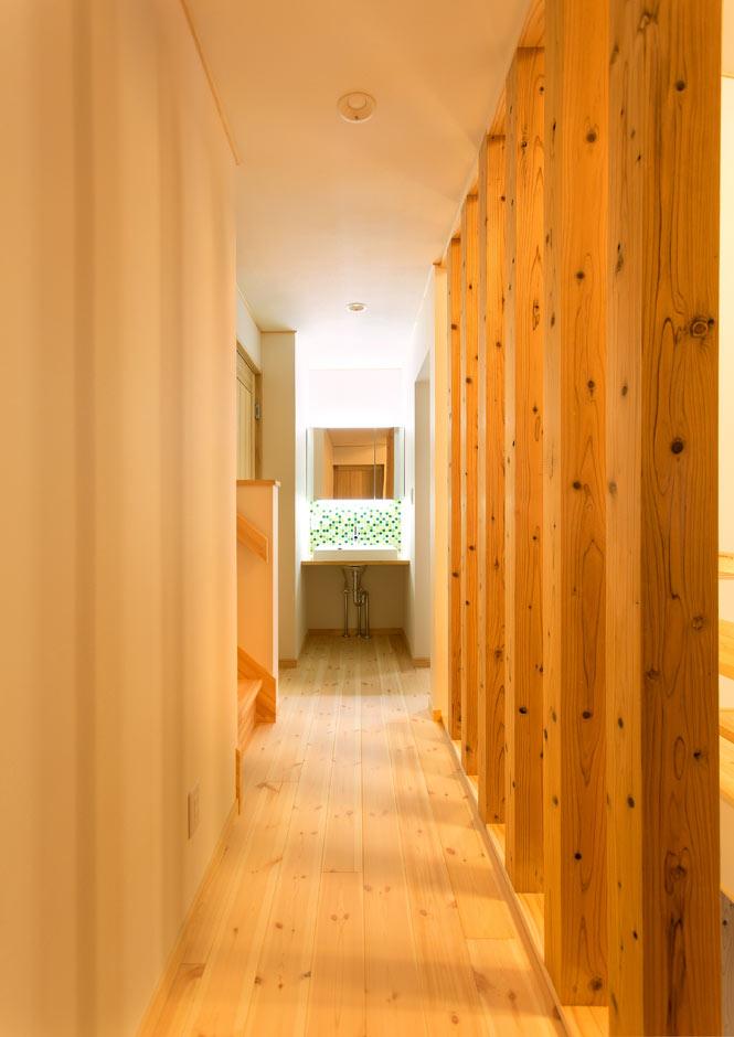 木の格子がニュアンスを与える2階の廊下。寝室の入口にドレッサーを設置し、華やかなモザイクタイルがアクセントに