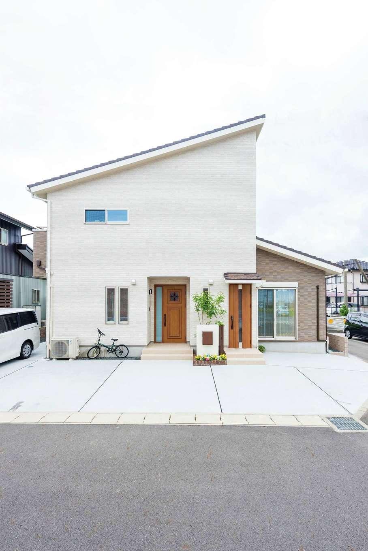 橋本組 ~つむぐ家~【子育て、二世帯住宅、間取り】片流れの屋根と仲良く二つ並んだ玄関が印象的。お母さまの居室部分は外壁の色を変えアクセントに