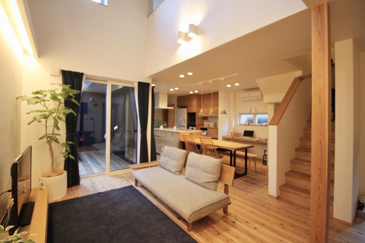 ツリーズ【デザイン住宅、自然素材、間取り】開放感あふれる、ダイナミックな吹抜けのLDK。両隣に住宅が迫っているため、高窓と中庭から光を取り込む。これだけの大空間でも、セルロースファイバーと遮熱塗り壁により家中の温度差がなく、夏も冬も快適に過ごせる。肌触りのいい床は無垢の杉、天井はウエスタンレッドシダー