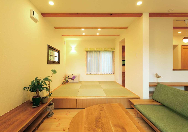 Casa(カーサ)【二世帯住宅、自然素材、間取り】リビングとキッチンの両方と繋がる、小上がりの和室。窓のカーテンを開けると、色鮮やかな竹林が見える
