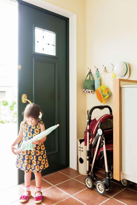 グリーンの玄関ドアとテラコッタタイルのコントラストがすてき