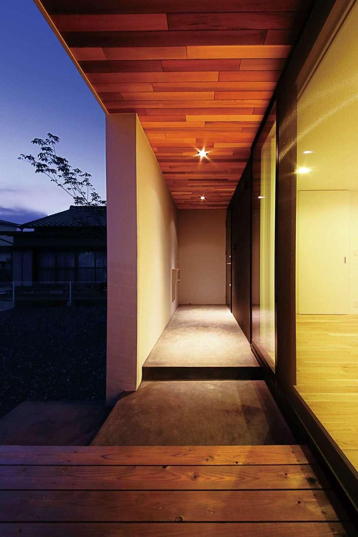 インフィルプラス【デザイン住宅、省エネ、間取り】壁で隠したアプローチと、リビングの前に設けたウッドデッキ。軒天はレッドシダー張り
