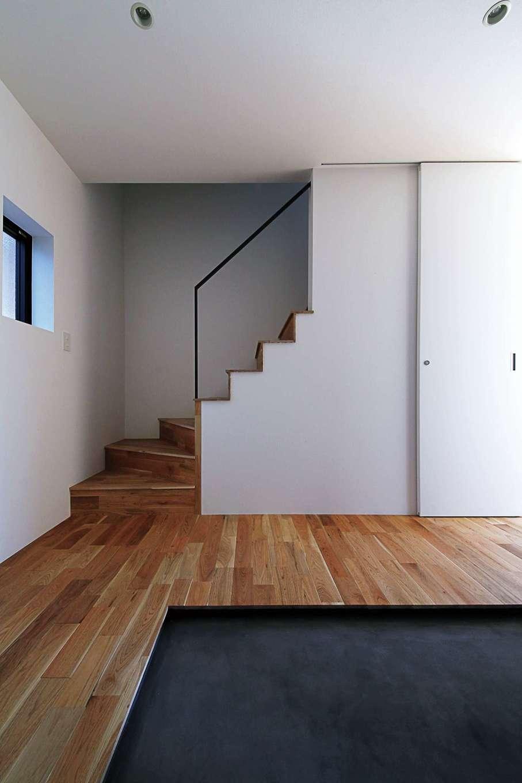 インフィルプラス【デザイン住宅、省エネ、間取り】モルタルの黒い土間とクルミの無垢の床が白壁に映える玄関。階段のアイアンの手すりや段々のラインが意匠性を高めている