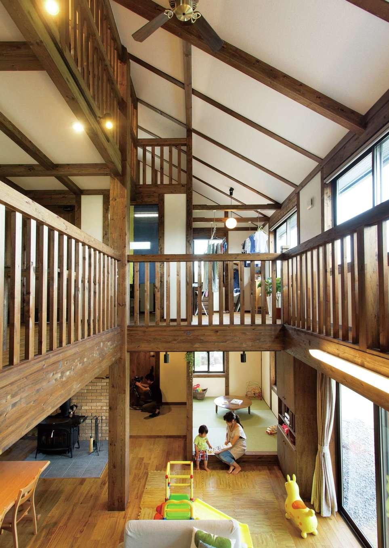 サイエンスホーム【デザイン住宅、自然素材、間取り】ご夫婦がどうしても欲しかった吹抜けのリビング。これほどの大空間でも外張り断熱による高気密・高断熱性能で上下階の温度差がなく、身体への負担が少ないと同時に、冷暖房効率を逃さないので光熱費も節約できる。柱と梁を現しにした真壁づくりと薪ストーブの相性も抜群
