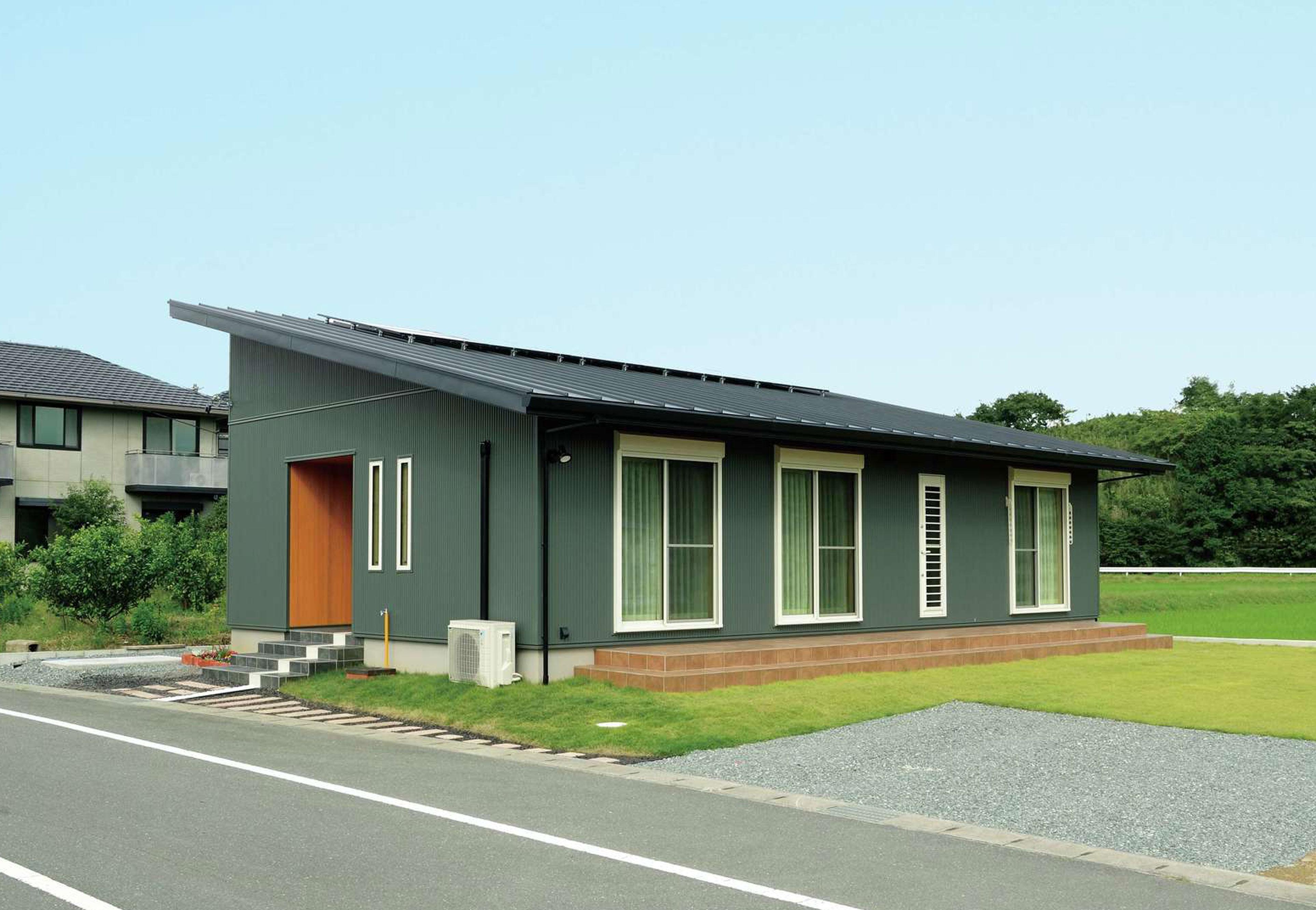 村木建築工房【自然素材、夫婦で暮らす、平屋】深緑の外壁と黒の屋根の組み合わせがモダンな外観。屋根には太陽光発電のパネルを搭載