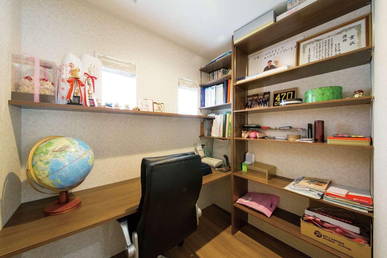 水田建設【趣味、省エネ、間取り】キッチンの奥に設けたご主人の書斎。壁面に棚を巡らせ、収納をたっぷり確保