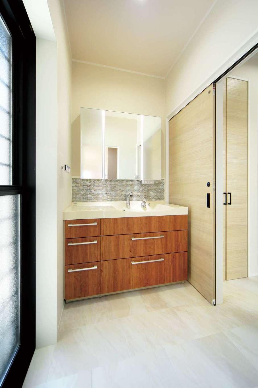 キッチンのすぐ隣にある洗面所の右手には浴室乾燥機付きのランドリールーム、左手ドアの外は物干し場。毎日実感する動線の良さ