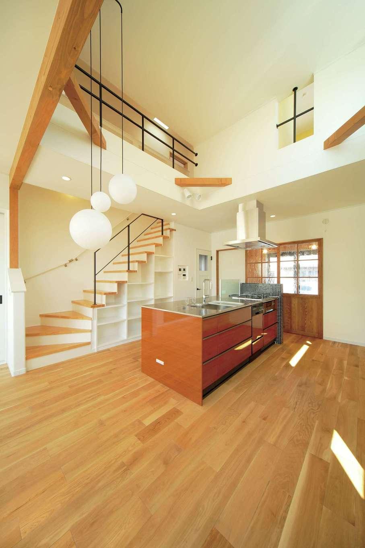 ココハウス【デザイン住宅、子育て、収納力】高い位置の窓から光が降り注ぐ吹き抜けのLDK。奥さまこだわりのステンレス天板のアイランドキッチンや、階段下、小屋裏など多彩な収納で、すっきりした暮らしが実現する。右手扉の向こうは土間。直接リビングに入れるスタイル