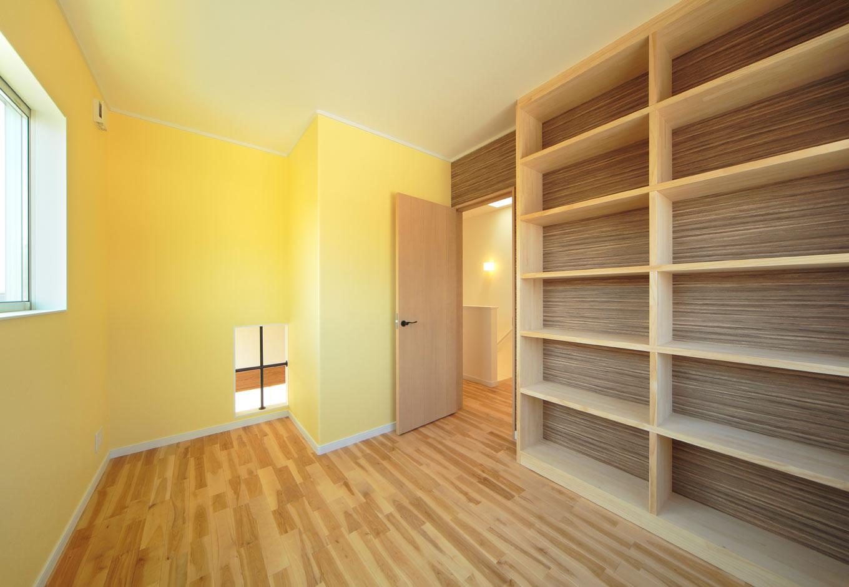 ココハウス【デザイン住宅、子育て、収納力】ご主人の書斎には壁一面に書架を造作。大量の蔵書が収納できる。壁紙はイエローで明るさを出した