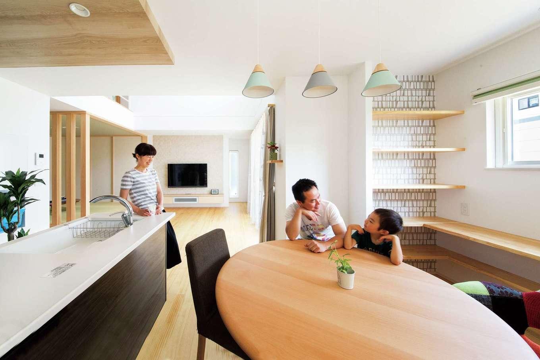 コットンハウス【子育て、省エネ、インテリア】ダイニングの丸テーブルは家族の団らんの中心。キッチンの天井のアクセントクロスにも注目!