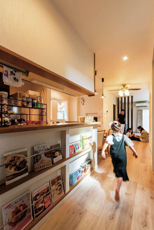 三和建設【子育て、間取り、スキップフロア】廊下に接するキッチンの壁には、料理本をたくさん持っているという奥さまの希望によって、マガジンラックを造作した。表紙がきれいな本や子どもの絵本をディスプレイして、お洒落なカフェのインテリアのように楽しんでいる
