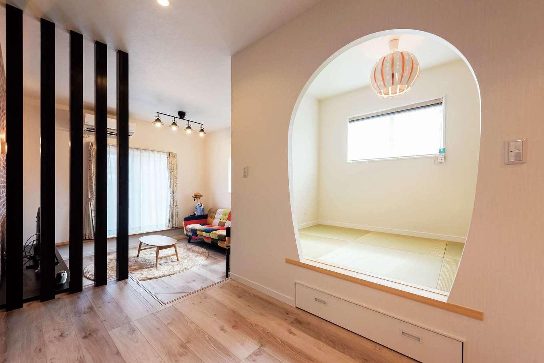 三和建設【子育て、間取り、スキップフロア】壁をアーチ状にくり抜いて、個性的な空間になった和室は、「多層空間®」のコンセプトを取り入れて小上がりに。腰掛けやすい高さが便利。純和風の空間にモダンな照明がアクセントに下部には引き出し収納を設けてある