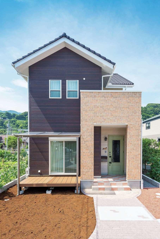 木とレンガを組み合わせたような、三角屋根がかわいい外観。バルコニーを載せた玄関ポーチで、雨の日の出入りも濡れずに快適。駐車場から伸びるアプローチ脇には、間もなく家庭菜園が誕生する
