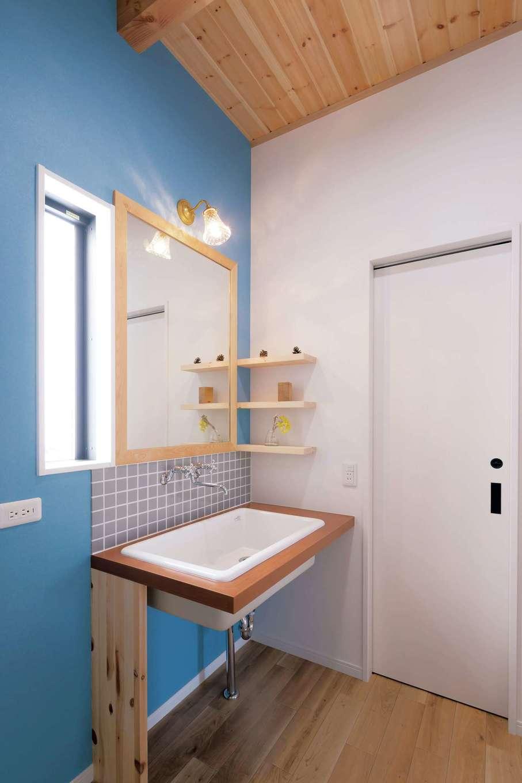 住まいるコーポレーション【デザイン住宅、自然素材、省エネ】ブルーのアクセントクロスにシンプルなデザインのオリジナル洗面台が映える。鏡も洗面台に合わせて造作したもの