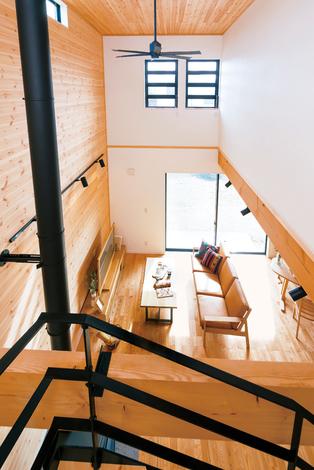 住まいるコーポレーション|大きな吹抜けのあるリビングはアイアンのストリップ階段や天井まで一面板張りの壁がアクセント