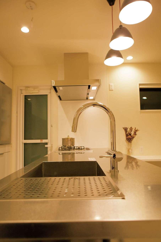 ARRCH アーチ【デザイン住宅、建築家、インテリア】オールステンレスで造作したオープンキッチンは、デザインと使い勝手を両立。ワークトップの下に椅子を置けばバーカウンターに早変わり。螺旋階段とのコントラストも美しい