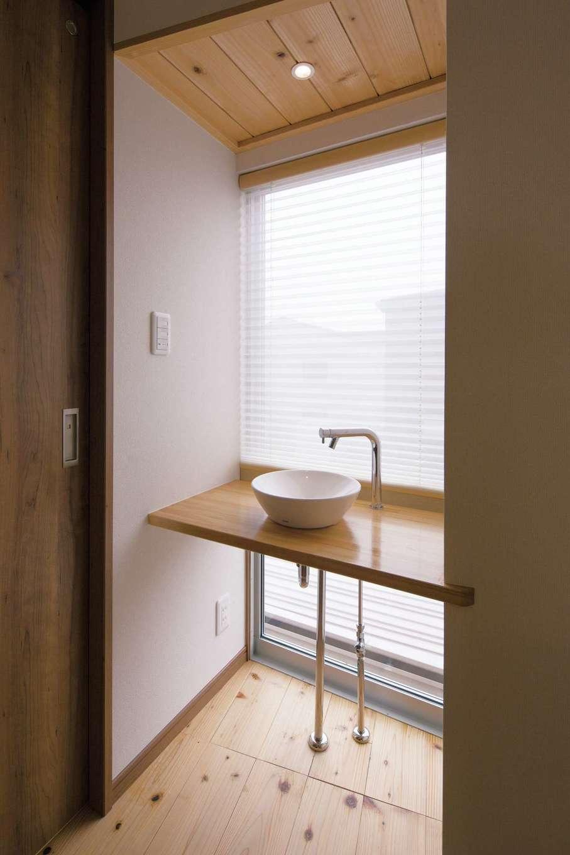 FIXの大きな窓から眺望を楽しめる2階の洗面台。無垢のカウンター、洗面ボウル、むき出しの水道管がバランス良く調和している