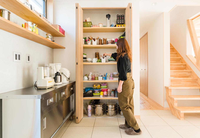 四季彩ひだまり工房 高田工務店【趣味、自然素材、間取り】キッチンのデッドスペースを活かして造作したパントリー。家族はもちろん、料理教室の生徒さんも取り出しやすいよう観音開きの扉を採用した