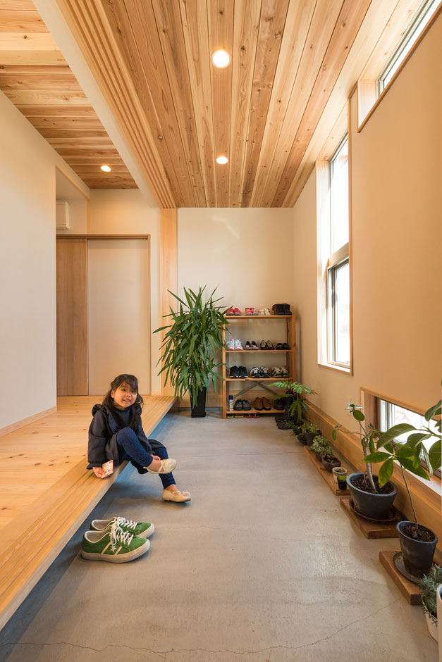 四季彩ひだまり工房 高田工務店【趣味、自然素材、間取り】新しいのにどこか懐かしい雰囲気が漂う土間玄関。手前からリビングへ行けるし、奥に進むとキッチンへつながるので、料理教室の生徒さんが来てもプライバシーを守ることができる。無垢と自然素材の効果なのか、新築してから観葉植物の成長が早まったそう