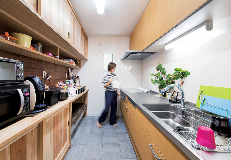 堀田建築【自然素材、和風、二世帯住宅】リビングの奥には独立したキッチンをレイアウトすることで、生活感を感じさせない。掃除に便利なタイルの床、食器棚を造作することで調理家電やゴミ箱などがぴったり収まり、家事もスムーズ