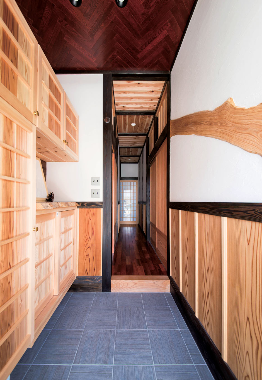 堀田建築【自然素材、和風、二世帯住宅】壁にケヤキの片木をあしらい、天井のヘリンボーン柄が印象的な玄関。廊下の床には縁起のよいカリンを使用