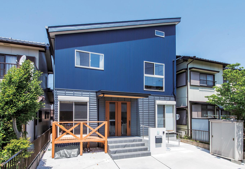 堀田建築【自然素材、和風、二世帯住宅】片流れ屋根に、1階は鎧張り風、2階は青色のガルバリウム鋼板を貼り分けた個性的な外観。玄関の庇をしっかり木組みすることで支えの柱をなくし、すっきりとした印象に。お母さまのためにスロープを設けている