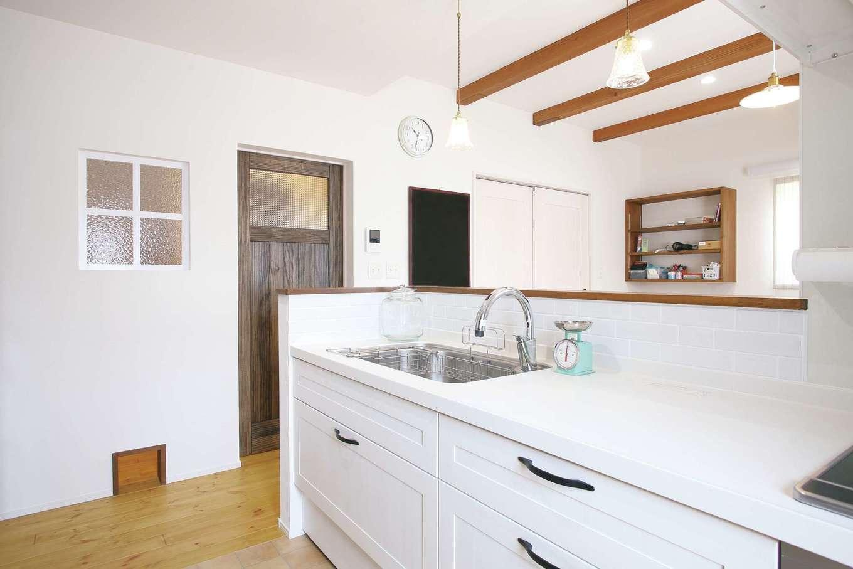 堀田建築【デザイン住宅、輸入住宅、自然素材】キッチンはワークトップから収納扉まで白で統一。壁に室内窓をつけることで、廊下にも光を取り込んでいる。下部のキャットドアは猫と暮らす必須仕様