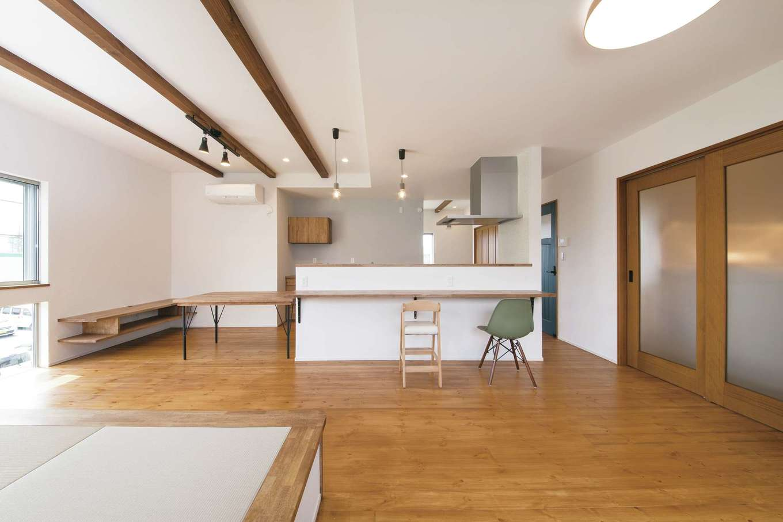 堀田建築【収納力、二世帯住宅、自然素材】自然塗料で仕上げたパイン材の床が心地よく、塗り壁はキッチン背面だけグレーに。小 上がりの畳コーナー、ダイニングテーブルなど、家具のすべてが大工のお手製